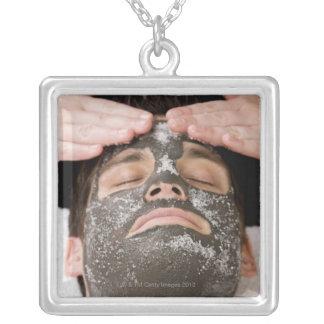 Applying skincare face mask with salt pendant