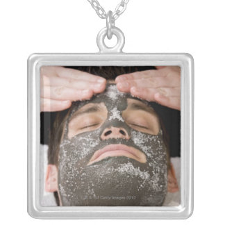 Applying skincare face mask with salt square pendant necklace