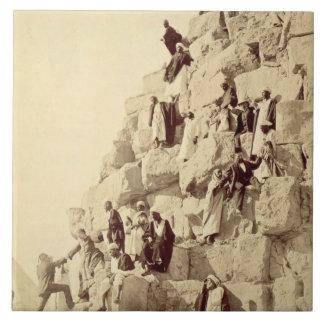 Árabes que ayudan a turistas para subir las pirámi azulejo cuadrado grande