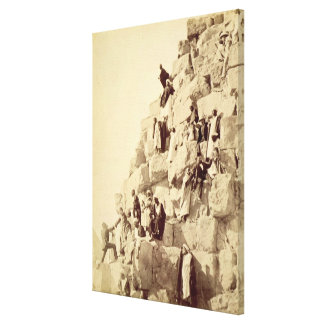 Arabs assisting tourists to climb the pyramids at stretched canvas prints