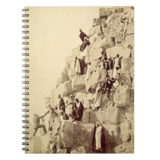 Arabs assisting tourists to climb the pyramids at note book