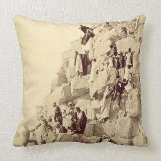 Arabs assisting tourists to climb the pyramids at throw pillow
