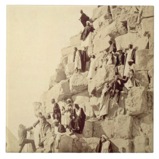Arabs assisting tourists to climb the pyramids at tile
