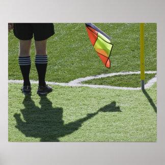 Árbitro del fútbol que sostiene la bandera póster