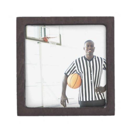 Árbitro que lleva a cabo baloncesto en corte cajas de regalo de calidad