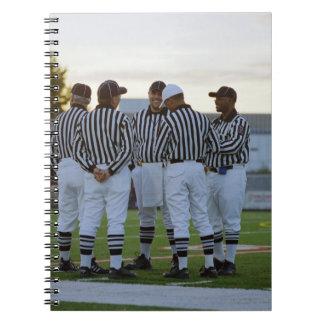 Árbitros del fútbol americano que hablan en campo libro de apuntes con espiral
