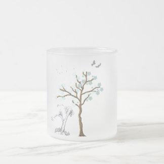 Árbol con las flores en fondo azul taza de café