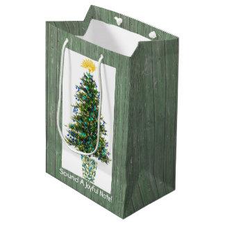 Árbol de navidad adornado con símbolos de música bolsa de regalo mediana