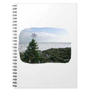 Árbol de navidad contra rocas de la playa cuaderno