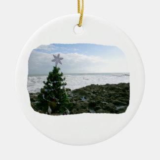 Árbol de navidad contra rocas de la playa adorno redondo de cerámica