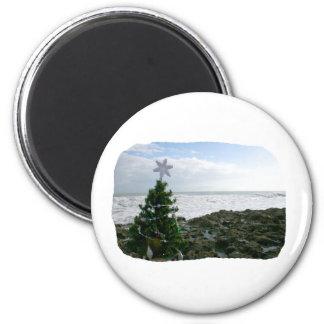 Árbol de navidad contra rocas de la playa imán redondo 5 cm