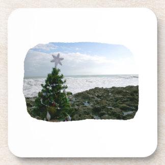 Árbol de navidad contra rocas de la playa posavasos de bebidas