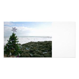 Árbol de navidad contra rocas de la playa tarjeta fotografica