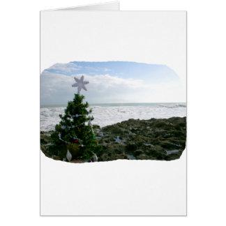 Árbol de navidad contra rocas de la playa tarjeta de felicitación