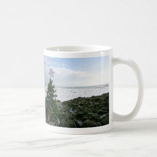 Árbol de navidad contra rocas de la playa taza