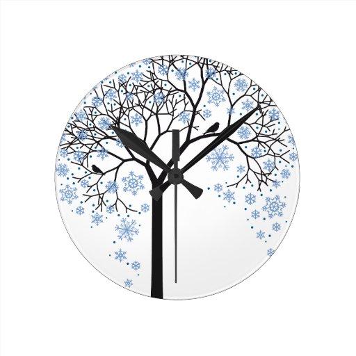 Árbol del invierno con los copos de nieve y los pá reloj