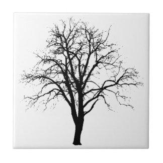 Árbol deshojado en silueta del invierno azulejos