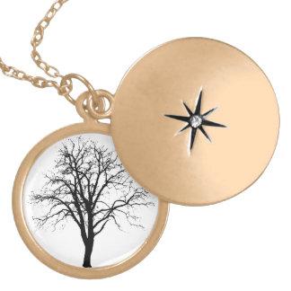 Árbol deshojado en silueta del invierno medallón