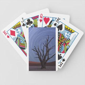 árbol desnudo de pintura en el viento que remolina cartas de juego