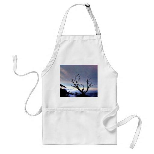 Árbol desnudo en orilla en la puesta del sol delantal