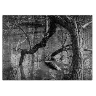 Árbol en el agua, fotografía oscura del horror, tabla para cortar