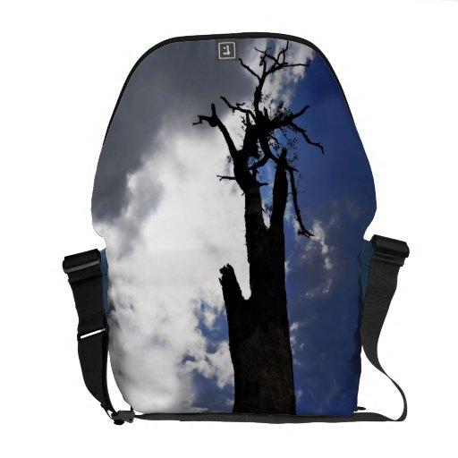 Árbol muerto viejo contra el cielo nublado oscuro bolsa messenger