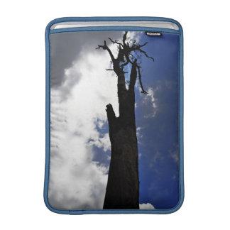 Árbol muerto viejo contra el cielo nublado oscuro funda  MacBook