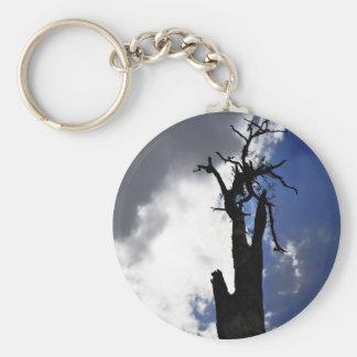 Árbol muerto viejo contra el cielo nublado oscuro llavero redondo tipo pin
