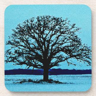Árbol solo en un paisaje del invierno posavasos