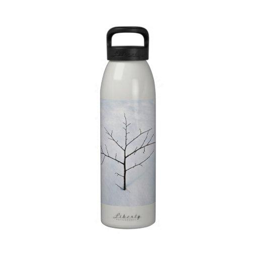 Árbol solo secado de la rama en un paisaje nevoso botellas de agua reutilizables