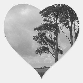 Árboles azotados por el viento pegatina en forma de corazón