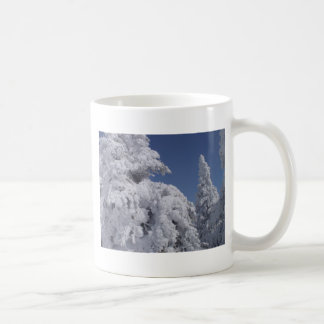 Árboles de la conífera enyesados con nieve taza básica blanca