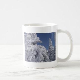 Árboles de la conífera enyesados con nieve taza clásica
