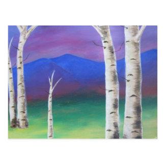 Árboles delante de mountians en la puesta del sol postal