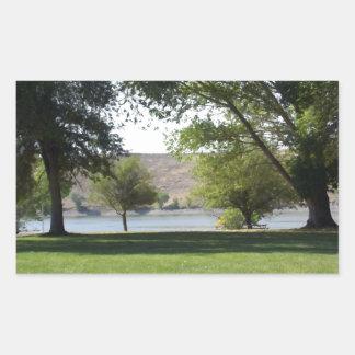 Árboles por el lago con el césped rectangular altavoz