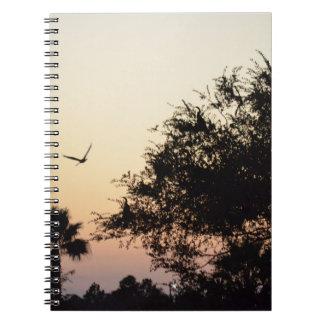 árboles y pájaro de vuelo contra la puesta del sol libreta espiral