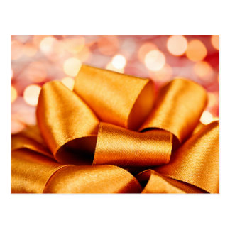 Arco del regalo del oro con las luces festivas postal