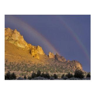 Arco iris doble sobre una formación de roca cerca postal