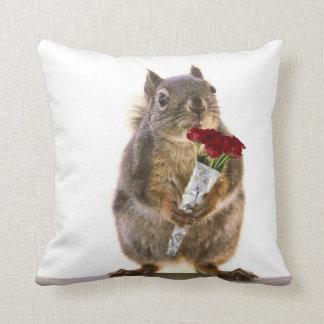 Ardilla que sostiene el ramo del rosa rojo almohada