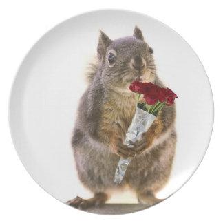 Ardilla que sostiene el ramo del rosa rojo plato de cena