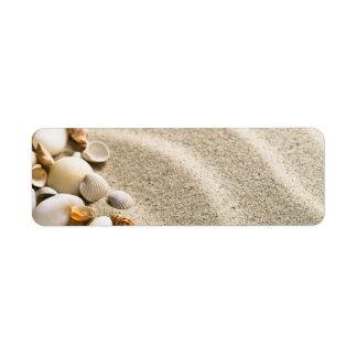 Arena con las cáscaras y las piedras. Composición  Etiqueta De Remite