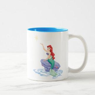 Ariel que se sienta en roca taza de dos tonos