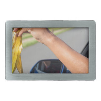 Arm dropping peel of banana out car window belt buckle
