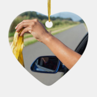 Arm dropping peel of banana out car window ceramic ornament