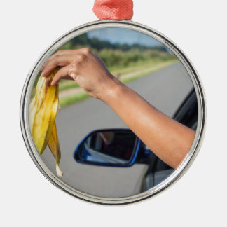 Arm dropping peel of banana out car window metal ornament