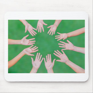 Arms of children together in circle on green mouse pad