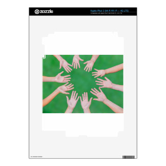 Arms of children together in circle on green skins for iPad 3