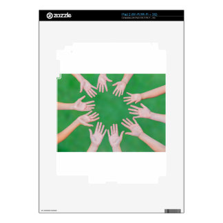 Arms of children together in circle on green skins for the iPad 2