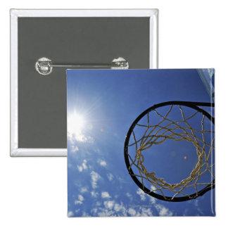 Aro de baloncesto y el Sun, contra el cielo azul Pin Cuadrado