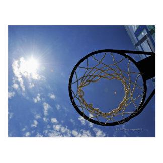 Aro de baloncesto y el Sun, contra el cielo azul Postal